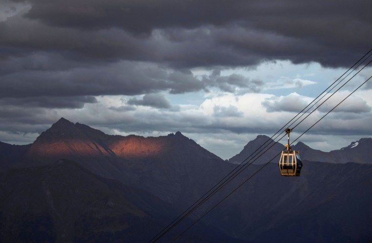 Image: A cable car is pictured with Caucasus mountains during sunset in the background outside Krasnaya Polyana near Sochi