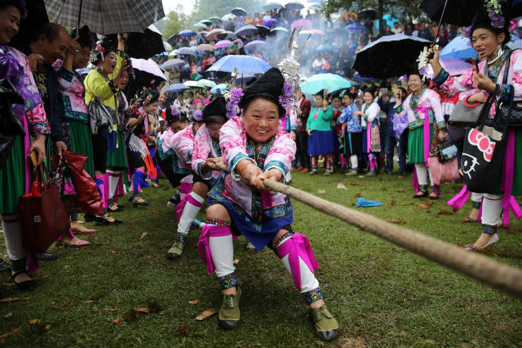 Image: Ethnic Miao women in traditional costumes take part in a tug of war to celebrate a local festival at a village in Rongshui Miao Autonomous County