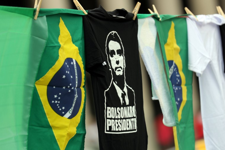 Image: National flags and shirts with the image of Brazil's presidential candidate Jair Bolsonaro are seen for sale in front of Pacaembu Stadium in Sao Paulo