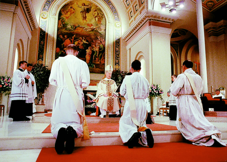 Newly ordained priests, including Christopher Clay, center, kneel before Bishop James Timlin at St. Peter's Cathedral in Scranton, Pennsylvania, in June 1998.