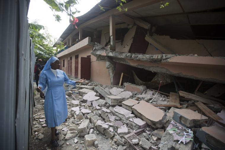 Sr Maryse Alsaint walks alongside a school damaged by a magnitude 5.9 earthquake in Haiti