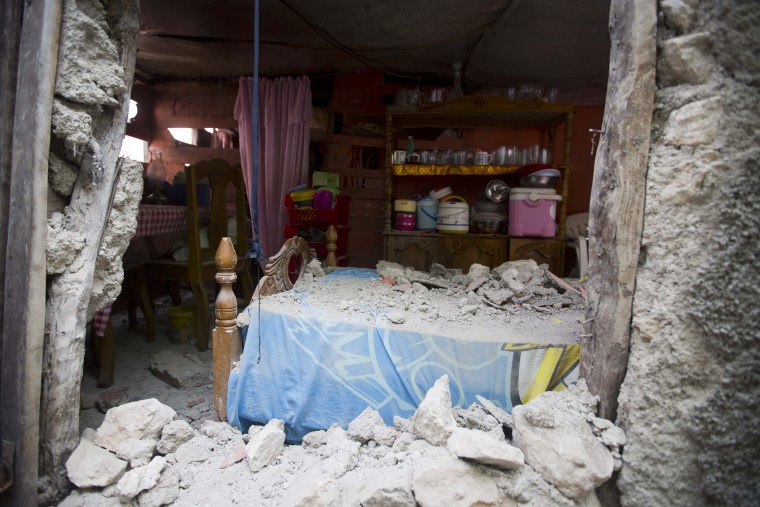 A bed is covered in rubble caused by a magnitude 5.9 earthquake the night before in Haiti