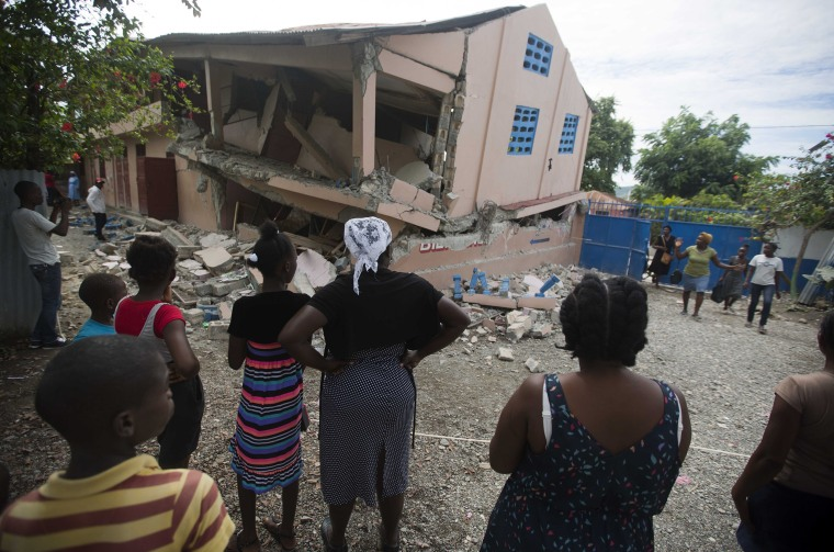 Residents look at a collapsed school damaged by a magnitude 5.9 earthquake the night before in Haiti