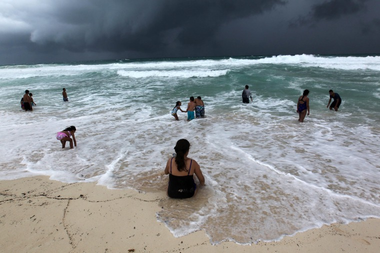 People swim in the turbulent sea at a beach in Cancun, Quintana Roo, Mexico