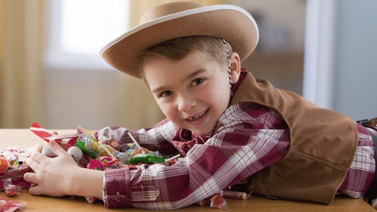 Boy in cowboy costume eating Halloween candy