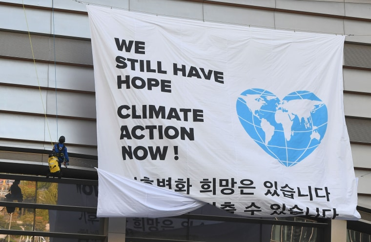 """Image: Greenpeace activists display a big banner reading """"We still have hope, Climate action now!"""""""