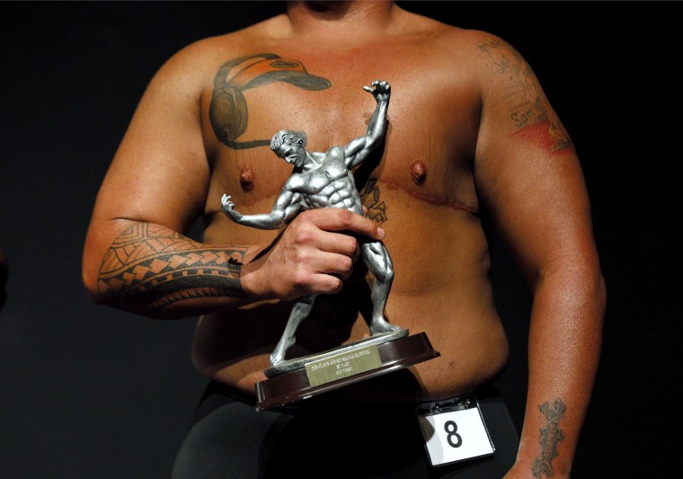 Image: Kennedy Conners, of Conyers, Ga., who transitioned from female a year and half ago, holds his trophy after winning the heavyweight class in the International Association of Trans Bodybuilders competition