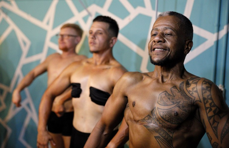Image: Charles Bennett, from right, of San Francisco, practices a pose in front of a mirror with fellow contestants Devyn Michael Clark, of Jacksonville, Fla., and Peter Moore, of Oakland, Calif., backstage before the start of the International Associatio