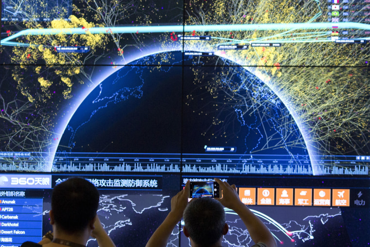 An attendee takes a photo of a visualization of global internet attacks during the 4th China Internet Security Conference in Beijing on Aug. 16, 2016.