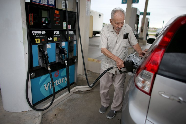 Image: Erwin Kerr pumps gas into his car from a pump with a sign indicating the gas is containing up to 10 % ethanol