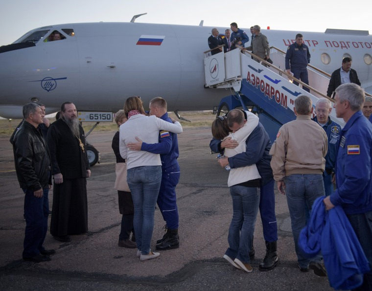 Cosmonaut Alexey Ovchinin, left, and NASA's Nick Hague, right, hug their families after landing at Baikonur Cosmodrome in Kazakhstan.