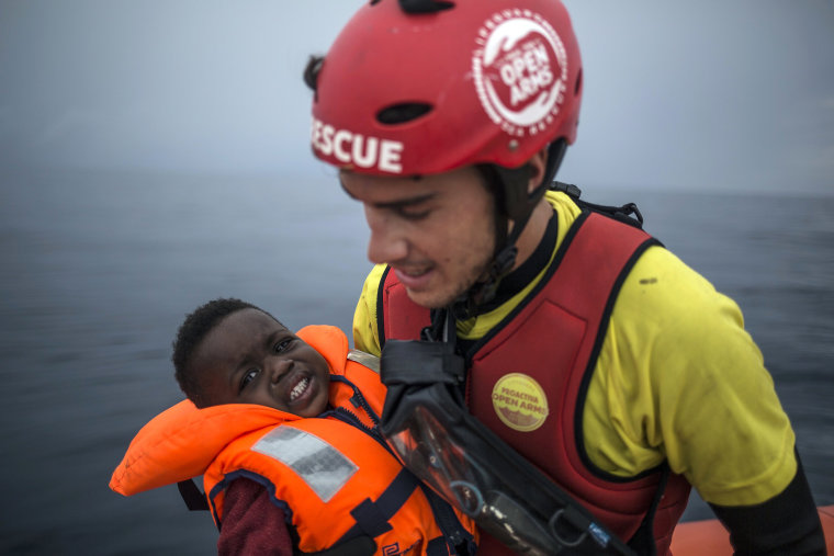 A member of Spanish NGO Pro activa Open Arms holds a baby rescued at a dinghy at Alboran Sea