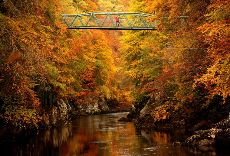 A woman stands on the footbridge over the river Garry near Pitlochry , Scotland