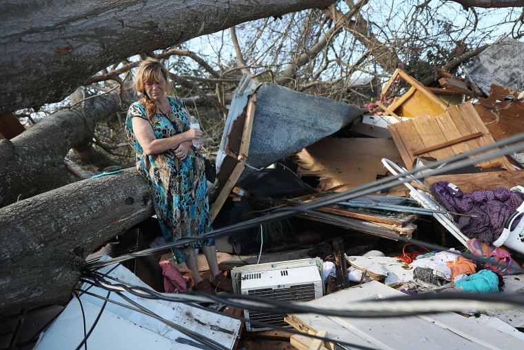 Kathy Coy stands among what is left of her home after Hurricane Michael destroyed it