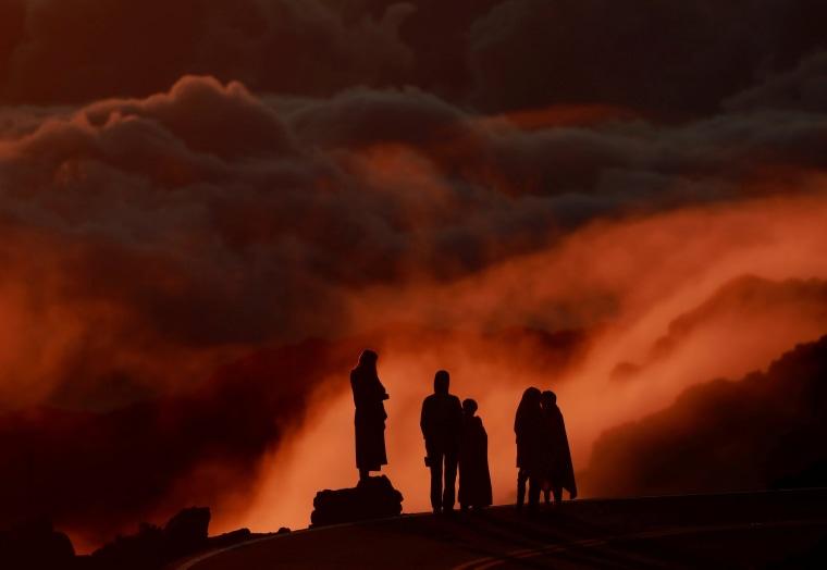 Light illuminates clouds as people watch the sunrise at Haleakea National Park in Hawaii