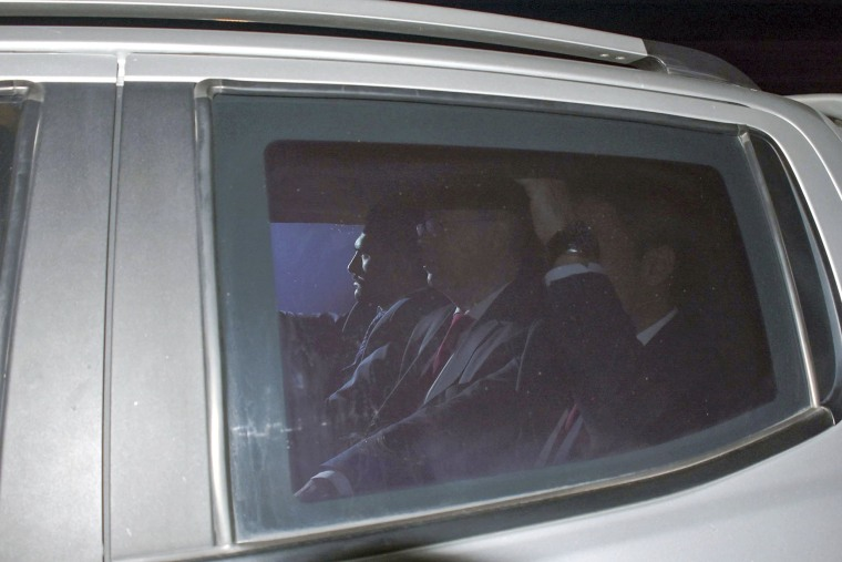 Image: Andrew Brunson, center, sits inside a car as he arrives for his trial in Izmir