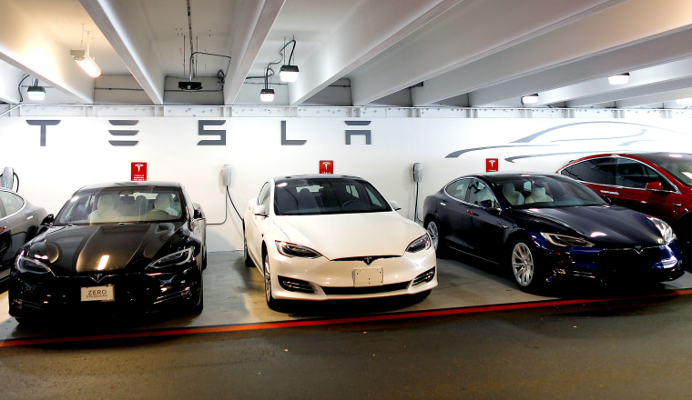 Image: Tesla Model 3s and X's are shown charging in an underground parking lot next to a Tesla store in San Diego,California