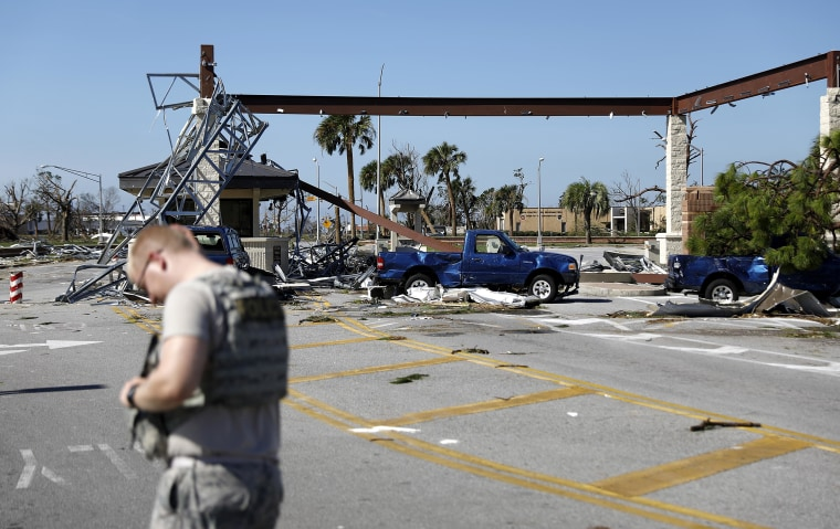 Image: A soldier stands guard at the damaged entrance to Tyndall Air Force Base in Panama City, Forida on Oct. 11, 2018, in the aftermath of hurricane Michael.