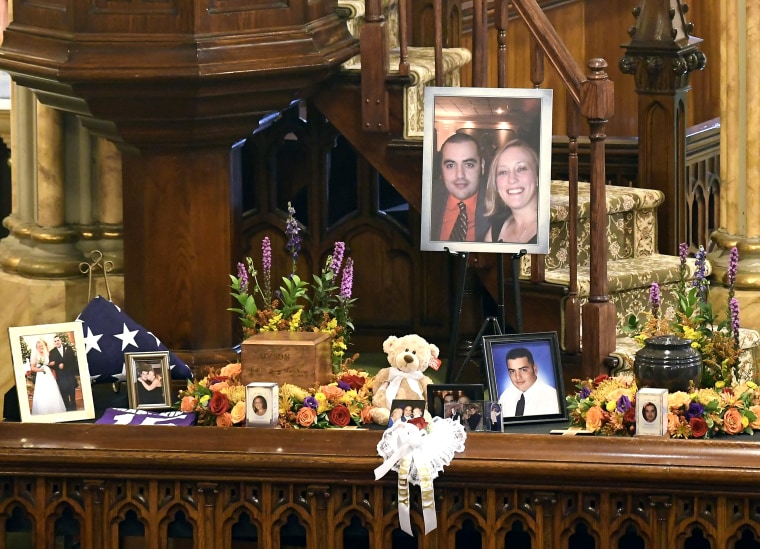 Image: A unity urn with cremated ashes of Robert Joseph Dyson and Mary E. Dyson is set in place as friends and family prepare for a funeral mass