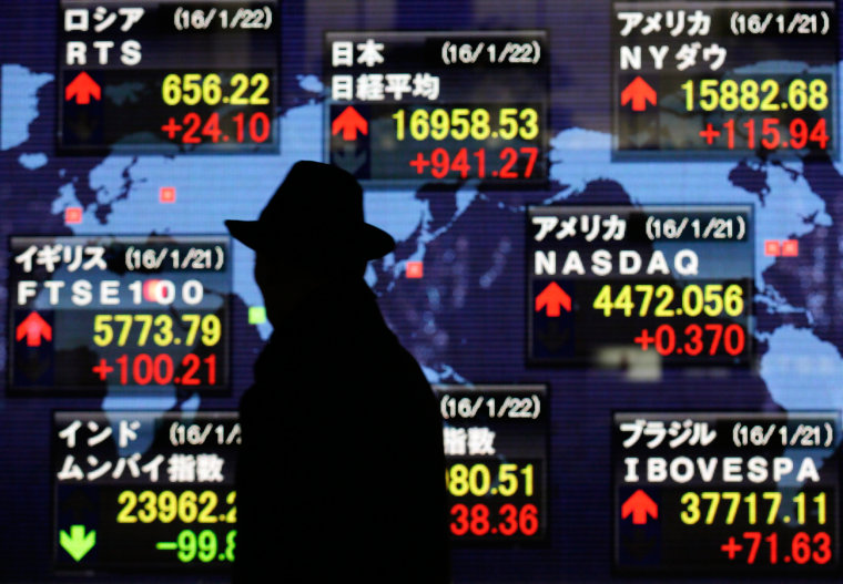 Image: A pedestrian watches closing information of Tokyo's Nikkei Stock Average and other global stock markets