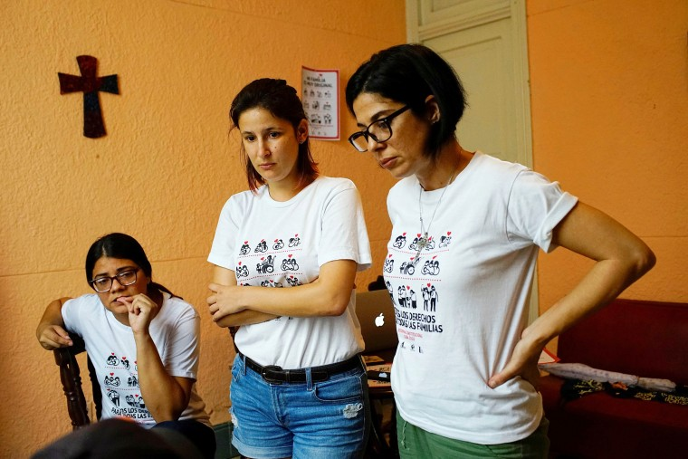 Image: Elaine Saralegui, Susana Hernandez and Angela Laksmi, activists supporting the lesbian, gay, bisexual and transgender community, talk to designers as they work in Havana