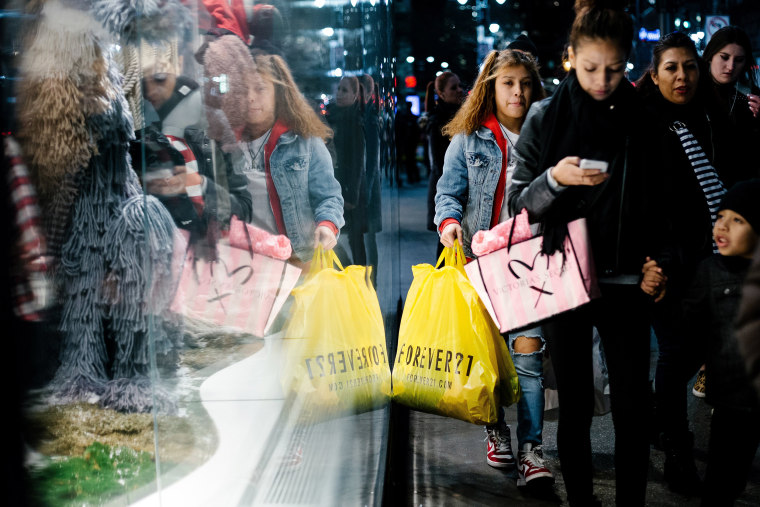 Image: People carry shopping bags outside a shopping mall