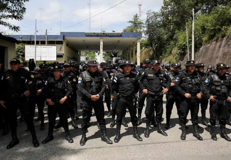 Guatemala's police officers stand as Honduran migrants, part of a caravan trying to reach the U.S., arrive to the border between Honduras and Guatemala