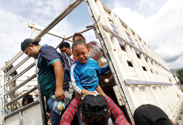 A Honduran migrant, part of a caravan trying to reach the U.S., cries as he gets off a truck during a new leg of their travel in Chiquimula
