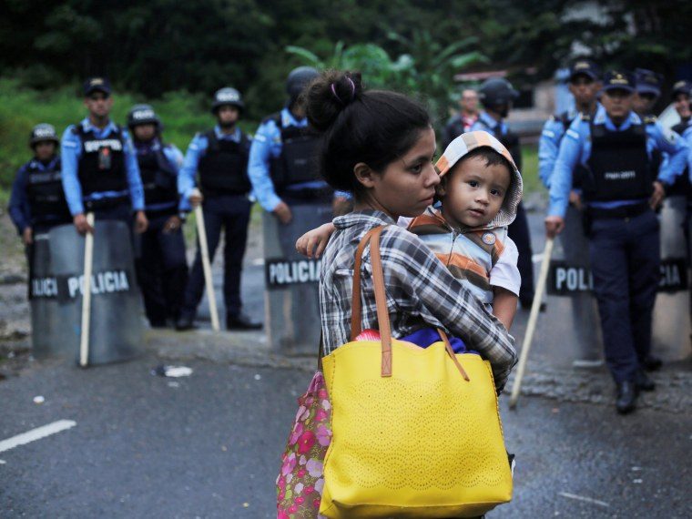 A Honduran migrant carries her baby in front of a police checkpoint near the Agua Caliente border while waiting to cross into Guatemala and join a caravan trying to reach the U.S., in the municipality of Ocotepeque
