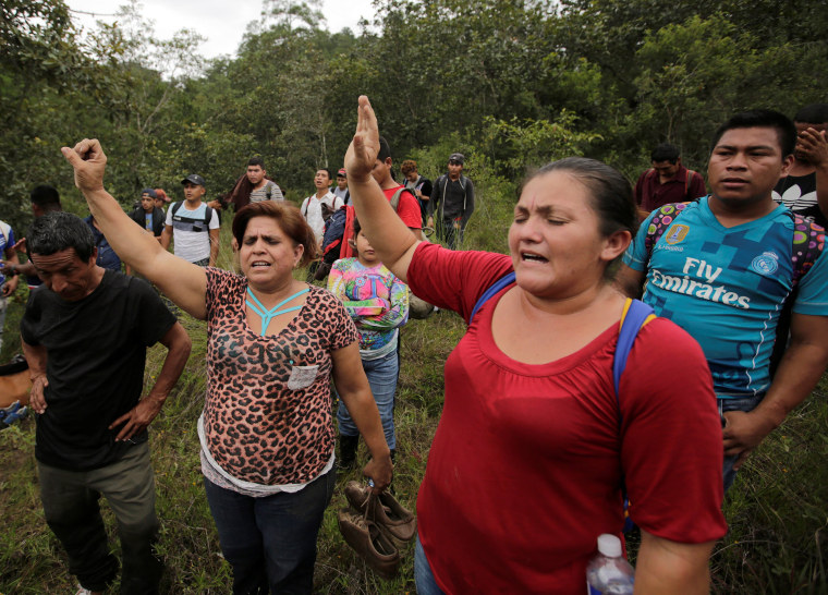 Honduran migrants pray after crossing into Guatemala, while hoping to join a caravan trying to reach the U.S, near Agua Caliente in Guatemala