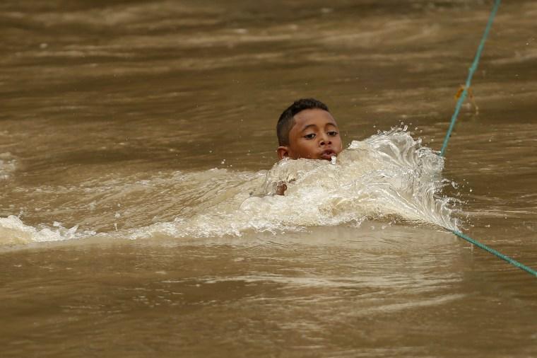 Honduran migrants cross border with El Salvador at Rio Goascoran