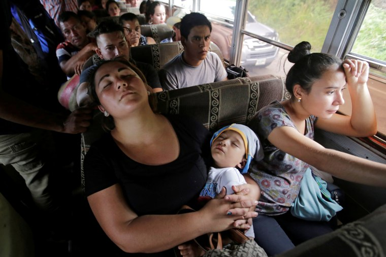 Image: A woman sleeps with her baby as they travel with fellow Hondurans fleeing poverty and violence on a bus in a caravan toward the United States, in the west side of Honduras