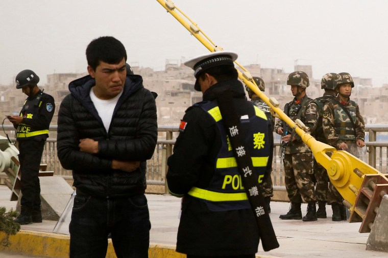 Image: A police officer checks the identity card of a man as security forces keep watch in a street in Kashgar