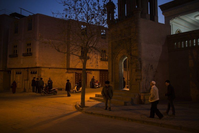 Image: Men congregate outside a mosque in the old city in Kashgar, Xinjiang.