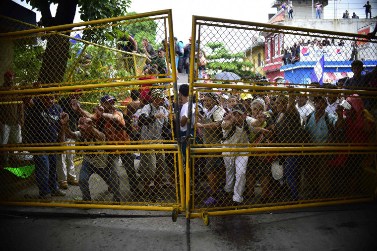 TOPSHOT - Honduran migrants heading in a caravan to the U.S. push to tear down the gate of the Guatemala-Mexico international border bridge in Ciudad Hidalgo, Chiapas state, Mexico, on Oct. 19, 2018.