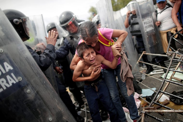 A Honduran migrant, part of a caravan trying to reach the U.S., protects her child after fellow migrants stormed a border checkpoint, in Ciudad Hidalgo