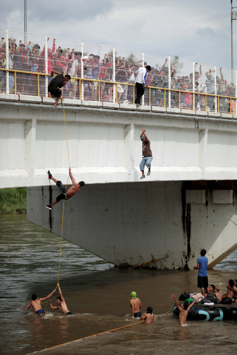 Honduran migrants jump and climb down from the bridge that connects Mexico and Guatemala to avoid the border checkpoint as others look while queued to enter Mexico in Ciudad Hidalgo
