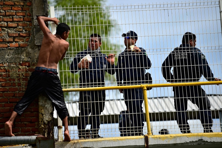 A Honduran migrant heading in a caravan to the U.S., prepares to jump to the Suchiate River from the Guatemala-Mexico international border bridge, near Mexican Federal Police officers, in Ciudad Hidalgo, Chiapas state, Mexico, on Oct. 20, 2018.