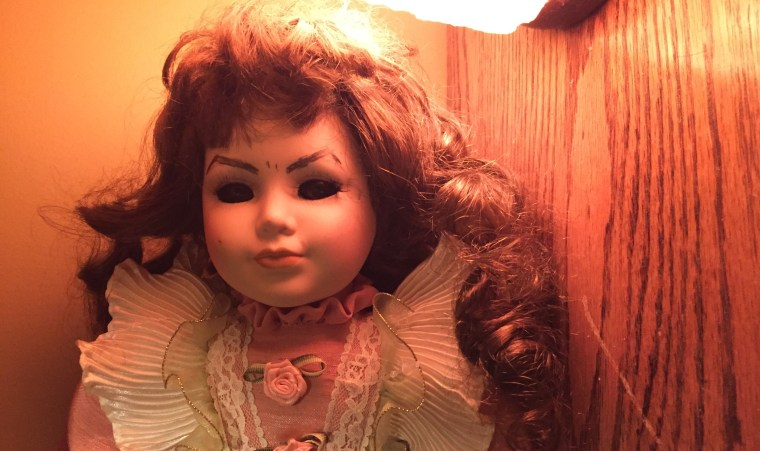 "Krystah Wright's daughter, Adele, 7, collects ""creepy"" porcelain dolls from thrift stores. After Adele threw this doll away because it ""scared her too much,"" Wright started hiding her around the house in different poses."