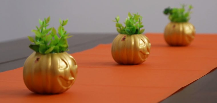 Use cheap pumpkin pails and fake plants to dress up your kitchen table