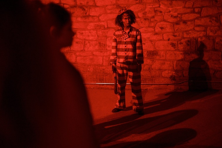 """Image: Ashley Mazyck, 26, awaits the next photo opportunity with visitors at the \""""Terror Behind the Walls\"""" haunted house on Oct. 24, in Philadelphia."""