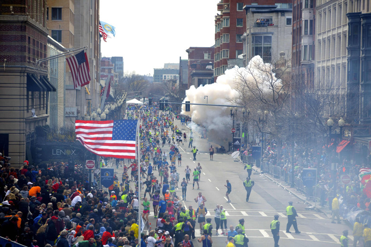 A bomb explodes in the crowd as runners cross the finish line during the 117th Boston Marathon