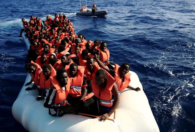 Image: An overcrowded dinghy with migrants from different African countries is followed by members of the German NGO Jugend Rettet as they approach the Iuventa
