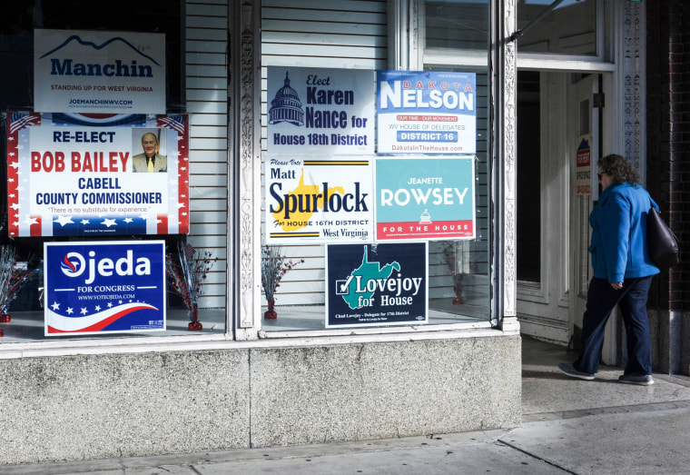 Image: A woman walks past election posters, one of them supporting Richard Ojeda, candidate for a US House seat in West Virginia