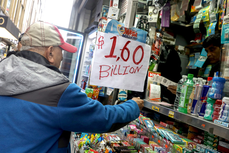 Image: A man buys tickets for Tuesday's Mega Millions lottery drawing after the jackpot exceeded $1.6 billion in New York City
