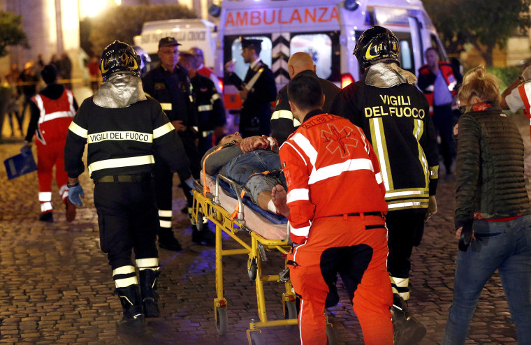 Image: Fire fighters and medical staff member carry an injured person outside the underground where some of CSKA Moscow supporters were injured in Rome