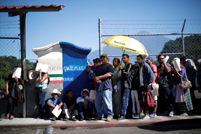 Image: Central American migrants queue at a border connecting Guatemala and Mexico while waiting to cross into Mexico, in Talisman