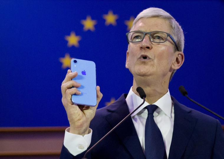Image: Apple CEO Tim Cook holds up an iPhone as he speaks during a data privacy conference at the European Parliament in Brussels