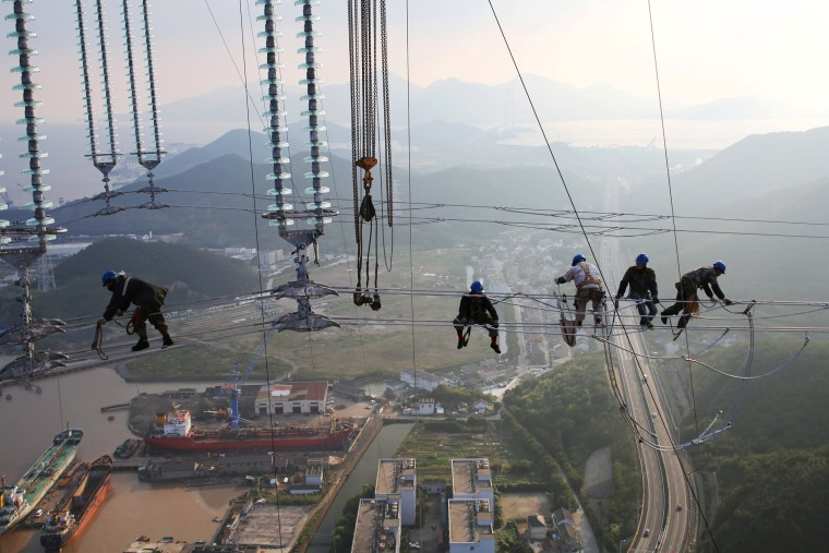 Image: Men work on cables connecting power transmission towers in Zhoushan