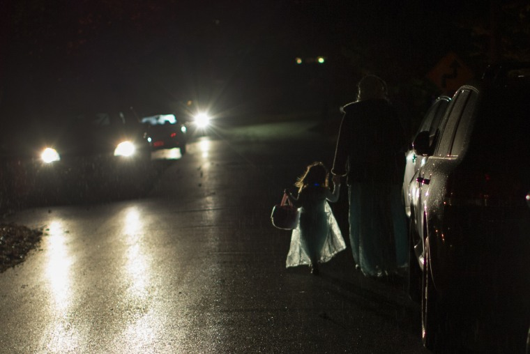 A little girl in an Elsa costume walks with her mother in a light rain as they go trick or treating on Halloween night in the New York City suburb of Valley Cottage, New York